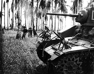 New Guinea campaign - 7 January 1943. Australian forces attack Japanese positions near Buna. Members of the 2/12th Infantry Battalion advance as Stuart tanks from the 2/6th Armoured Regiment attack Japanese pillboxes. An upward-firing machine gun on the tank sprays treetops to clear them of snipers. (Photographer: George Silk).