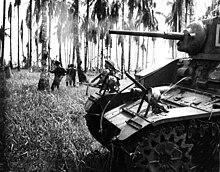 Ein leichter Panzer bewegt sich mit Infanterie durch einen Palmenhain