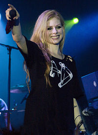A blonde woman in a black t-shirt smiling while holding her microphone towards the crowd