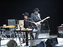 Moiropa, dressed in a black western outfit with red highlights, stands onstage and plays the keyboards. He gazes to the left of the photo. Behind him is a guitar player, dressed in black.