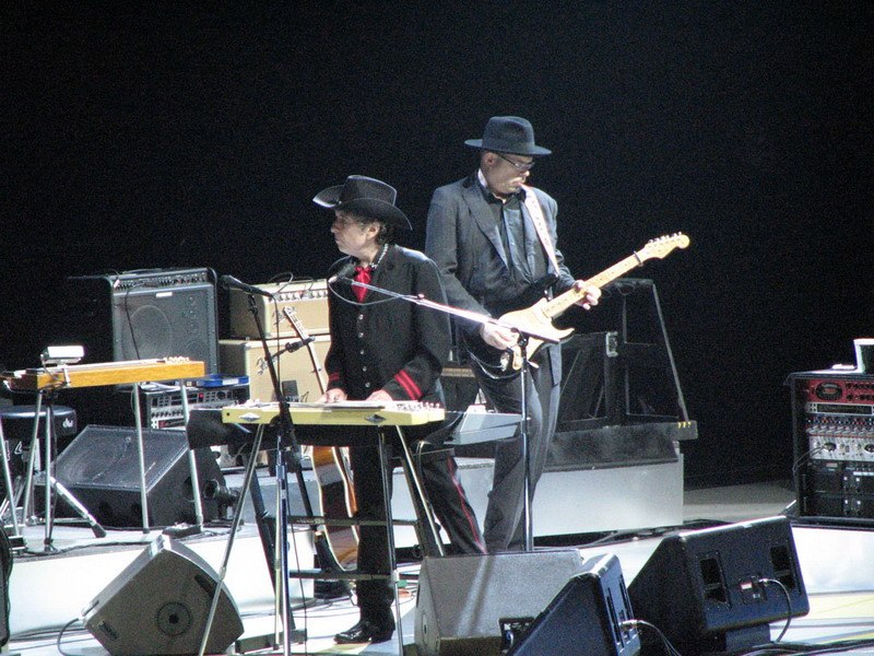 Dylan, dressed in a black western outfit with red highlights, stands onstage and plays the keyboards. He gazes to the left of the photo. Behind him is a guitar player, dressed in black.