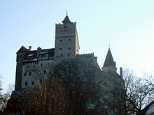 Vue en contre-plongée d'un château moyenâgeux avec son donjon au centre.