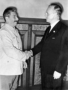 Two smiling men shake hands. Man on left wears a white suit and holds a cigarette. Man on right wears a black suit.