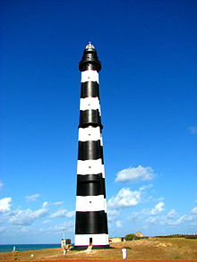 A black-and-white striped lighthouse, with the sea in the background