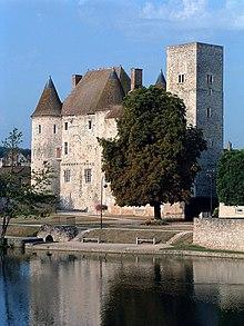 Photo d'un château à tours rondes et à donjon carré au bord d'une rivière