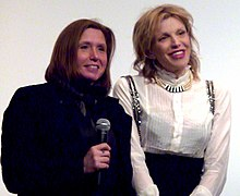 Two women facing an audience, holding microphones
