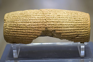 Cyrus Cylinder - Rear view of a barrel-shaped clay cylinder resting on a stand. The cylinder is covered with lines of cuneiform text