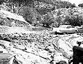 Debris swept into parking area at dormitory by flood. Partially marooned car, ranger dorm. ; ZION Museum and Archives Image ZION (7572dd4744ed4db8a2b6416cd9c34a16).jpg