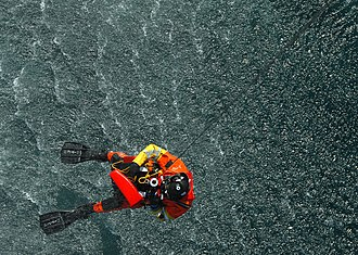 Aviation Survival Technician - A rescue swimmer from Coast Guard Air Station Cape Cod, Massachusetts, is hoisted back into an HH-60 Jayhawk after retrieving a rescue training dummy.