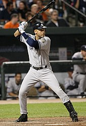 "A man preparing to bat on a baseball field. He is wearing a gray jersey and pants and a dark blue batting helmet; the jersey has a blue ""NEW YORK"" in the front, and the helmet has a white interlocking ""N"" and ""Y"" logo."