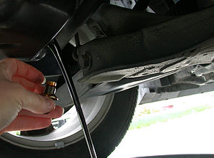 Draining the motor oil out of an automobile as...