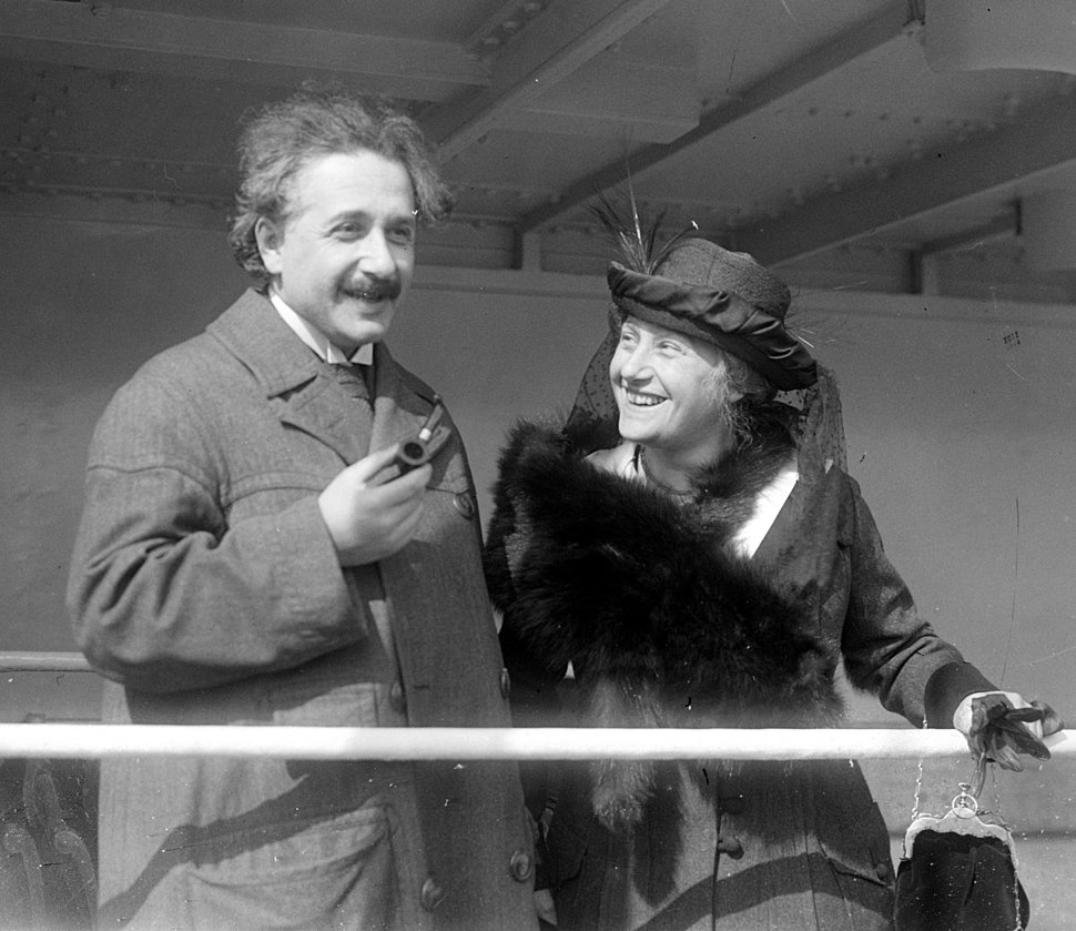 Einstein, looking relaxed and holding a pipe, stands next to a smiling, well-dressed Elsa who is wearing a fancy hat and fur wrap. She is looking at him.