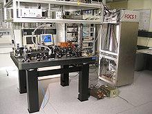 Laboratoriotablo per kelkaj optikaj aparatoj sur ĝi.
