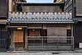 Facade of a dwelling with sudare, wooden balustrades and yellow lamp, Shinbashi-dori, Gion, Kyoto, Japan.jpg