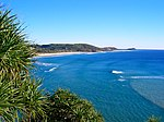 A grassy hilltop overlooking a shallow sand beach, with thick forests in the background
