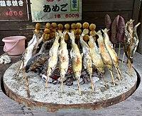 Freshly caught ayu (sweetfish) roasting on sticks, Nishiiyayama, Tokushima Prefecture, Shikoku, Japan.jpg