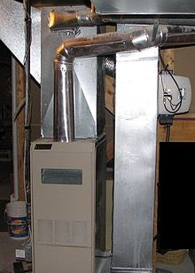 A photo of a modern forced-air gas furnace with associated ductwork nearby.