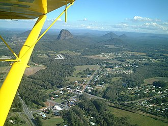 Glass House Mountains - Aerial photo of Glass House Mountains township with the Glass House Mountains in the distance