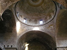 Bare interior of the former church of Hagia Irene in Istanbul showing the convergence of four short barrel vaults at the pendentives, windowed drum, and main dome