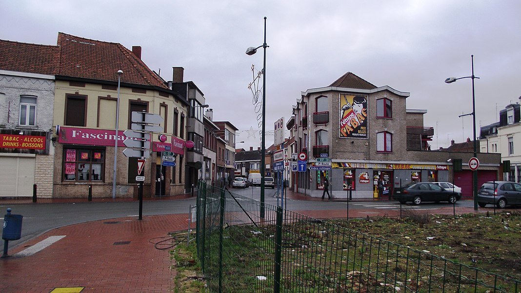 Border between France and Belgium in the border towns of Halluin (French) and Menen (Belgium). The derelict rigth corner is French (The buildings have been demolished in 2010, zie GE). The other side of the road is Belgian. Only the white on the far-rigth is French again. The shop advertises Belgian smokingware prices.