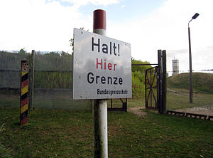 "A white sign on a post with the German inscription ""Halt! Hier Grenze"" (Stop! Here border) and below, in smaller letters, ""Bundesgrenzschutz"" (Federal Border Guard). In the background a wire fence with an open gate, behind that are trees and a watchtower on the skyline."