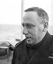 Informal head-and-shoulders portrait of man in dark coat and sweater, smoking a pipe