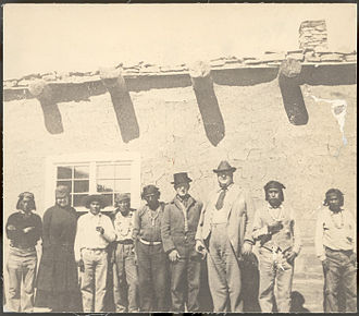 Frederick Webb Hodge - Thea (Mrs. George) Heye (second from left), Frederick Webb Hodge (1864-1956, MAI staff member, sixth from left) and George Gustav Heye (seventh from left) posed outdoors with Zuni Indians in front of a plastered adobe structure with vigas and rocks along roof line.