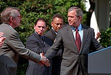President George W. Bush stands in front of a presidential podium. Standing behind him is a Hispanic-Native American man who is applauding.