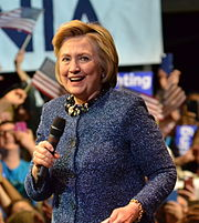 Hillary Clinton, a 68-year-old white woman with blonde hair, holding a microphone and wearing a blue suit.