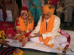 Culture of India - A Hindu wedding ritual in progress. The bride and the groom are seated together, receiving instructions from the priest. The sacred square fire container (yajna kund) is behind the priest.