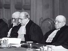 Three men in judge's robes seated at a bench, the middle one speaking