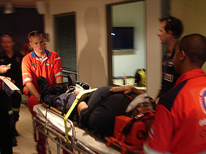 Paramedics wheeling a patient out strapped on ...