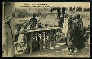 Indigénat - A customary court in French West Africa, c. 1920.  Note the native judges are wearing traditional French judges' hats.  A uniformed Guard de Cercle stands in the background.