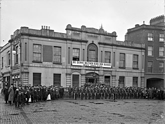 "Liberty Hall - Members of the Irish Citizen Army outside the original Liberty Hall, beneath a banner that reads ""We Serve Neither King nor Kaiser, But Ireland."""