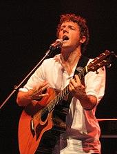 Buklohara viro, tintigante gitaron kaj portantan blankan ĉemizon.