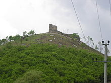 Old castle seen from downhill, with power lines in the foreground