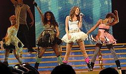 A brunette teenager singing into a microphone from a right profile. She is wearing a white dress with a tutu bottom. Behind her are background dancers in a stage with heavy lighting.