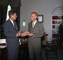 John F. Kennedy donante al John Glenn malgrandan amerikan flagon