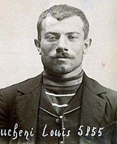 Photographie en noir et blanc d'un homme au visage légèrement souriant, portant une veste et un gilet avec un col en V qui laisse entrevoir un tricot rayé, ses cheveux sont coupés court.