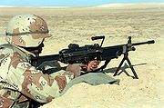 A U.S. Marine with an M249 SAW on its bipod manning a foxhole during the Persian Gulf War