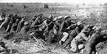 Scena wojny burskiej.  Mężczyźni w każdym wieku, noszący kapelusze i bandole, kucają w szeregu, z wycelowanymi karabinami