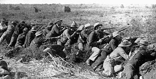Boer War scene. Men of all ages wearing hats and bandoleers crouch in a line, rifles pointed