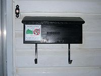 A black rectangular mailbox attached to the outside of a house. There is a doorbell above and to the left of the mailbox.