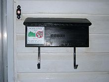 A Black Rectangular Mailbox Attached To The Outside Of House There Is Doorbell