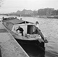 Man en vrouw aan het werk in de kuip van een woonboot die is afgemeerd aan een k, Bestanddeelnr 252-9393.jpg