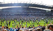 Photo des supporters envahissants le terrain du stade de Manchester City à la fin du match face à QPR, en 2012.