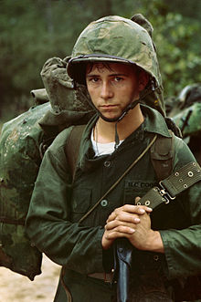 A photograph of a young United States Marine Corps private waiting against the backdrop of a jungle