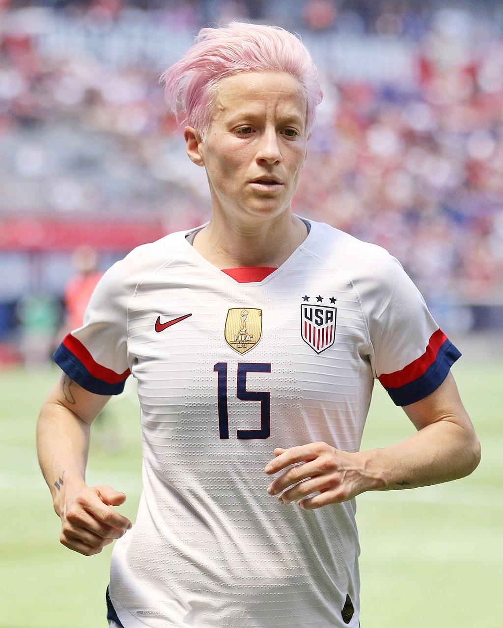 Megan Rapinoe corriendo en el campo de fútbol con la camiseta de la selección de fútbol estadounidense.