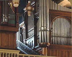 The metal pipes of two organs are in wooden cases of different dates and styles in the organ loft. To the side of the organ is a mosaic showing God as creator.