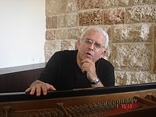 Moshe Zorman sitting in front of his piano